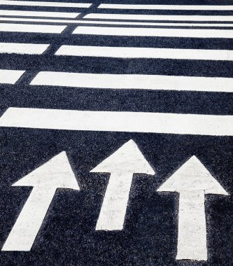 Zebra crossing with white marking lines and direction of motion