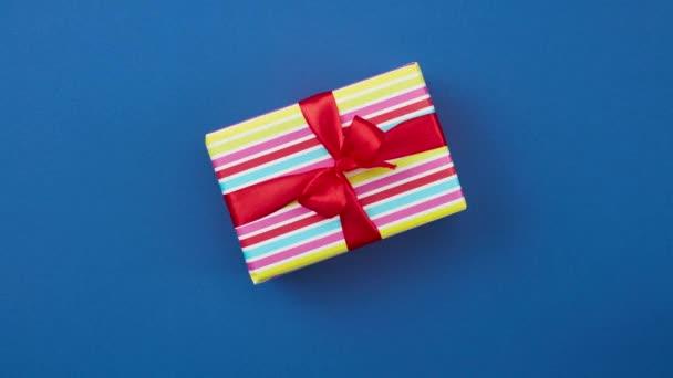 bunt verpackte Geschenkbox mit roter Schleife bewegt sich auf blauem Hintergrund, Draufsicht, Stop-Motion-Animation