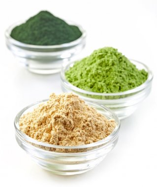 three bowls of various superfood powders