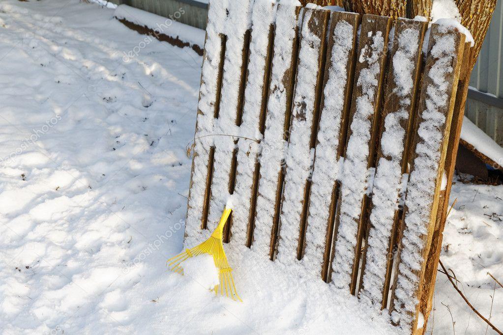 Yellow rake under snow in winter day