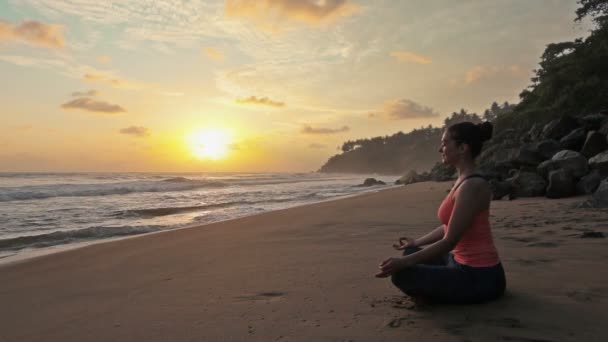 Woman meditating at beach on sunset