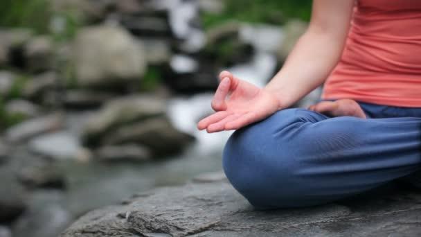 Zblízka ženy dělá jógu padmásaně lotus pose