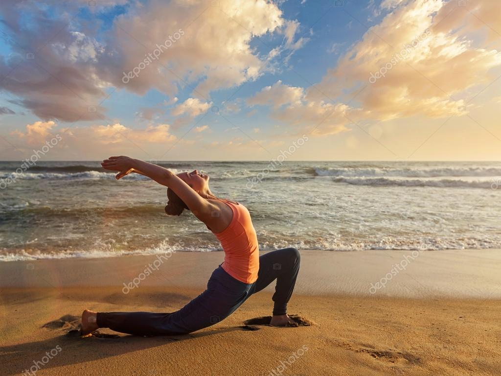 Sporty fit woman practices yoga Anjaneyasana at beach on