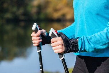 Closeup of womans hand holding nordic walking poles