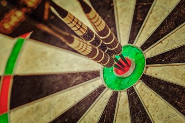 Three darts in bulls eye close up