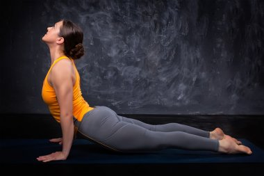 Sporty fit yogini woman practices yoga asana Urdhva mukha svanas