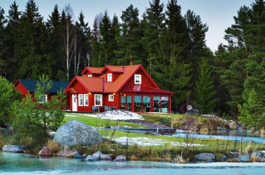 Red northern house in forest