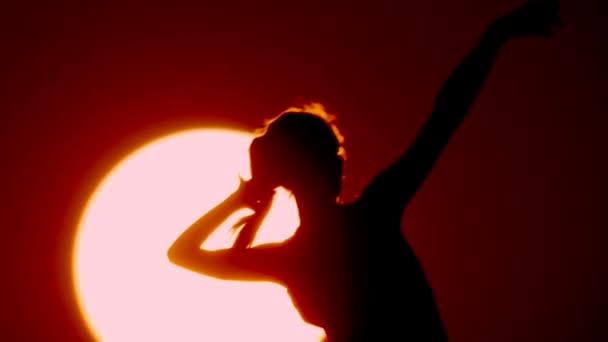 glückliche freie Frau, die den Sonnenuntergang im Meer genießt. Silhouette gegen den Sonnenuntergang, Sonnenaufgangssonne auf der Handfläche