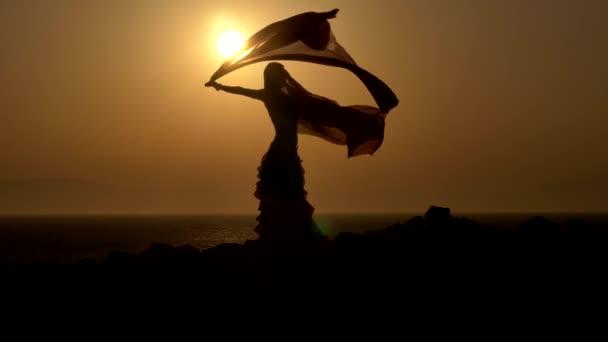 a sziluettje a gyönyörű naplemente egy nő-hastánc