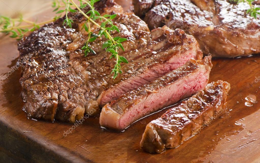Beef steaks on wooden board.