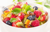 Bowl of  healthy fresh fruit salad with honey.