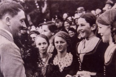 Adolf Hitler talking to young girls during a meeting