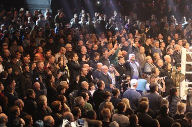 People sing the National Anthem before boxing fight