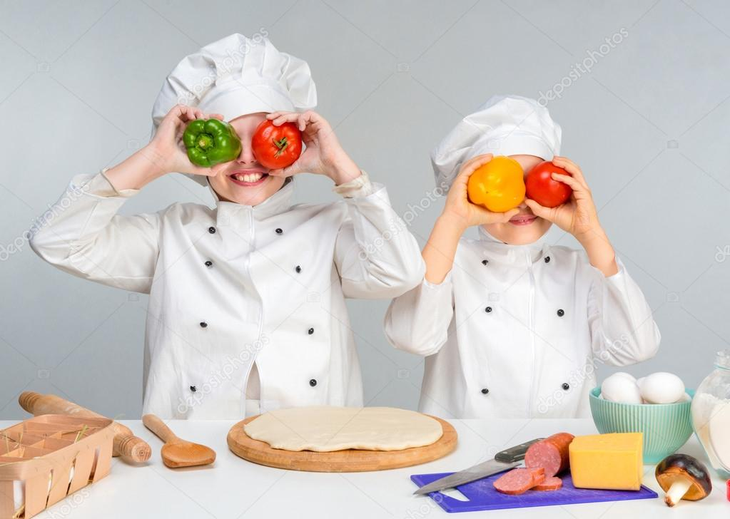 boy and girl in white uniform by the table prepare pizza