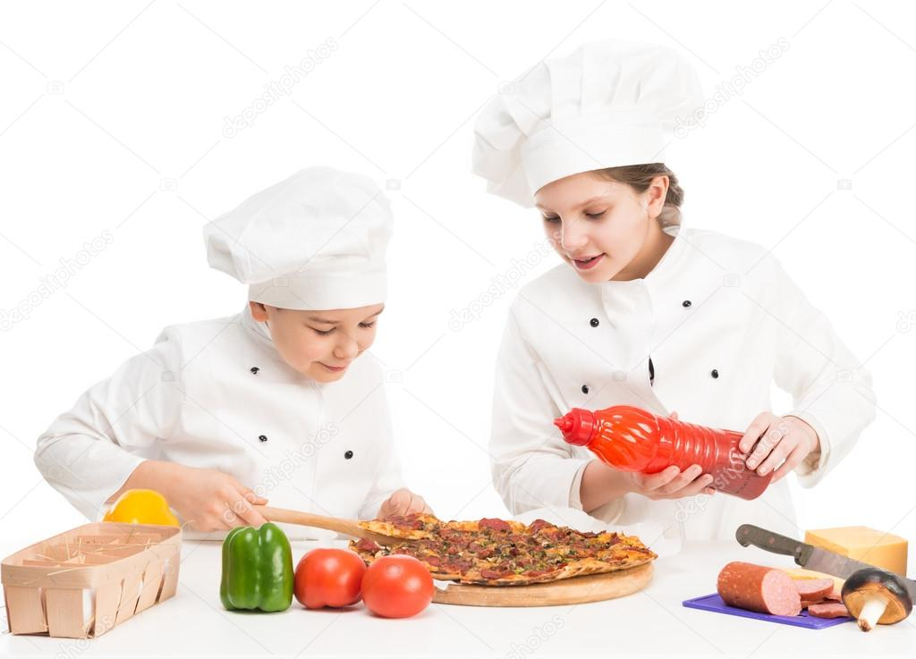 boy and girl in white uniform by the table with pizza