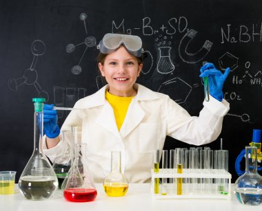 schoolgirl in white gown doing experiments with liquids