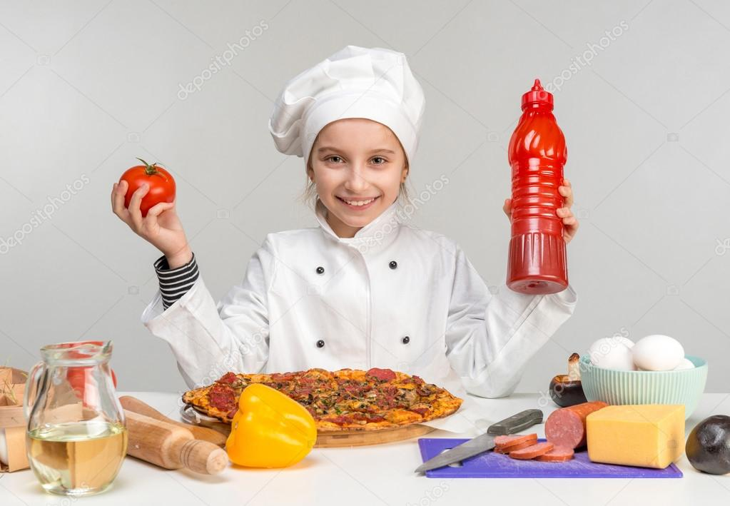 little girl pour pizza with ketchup
