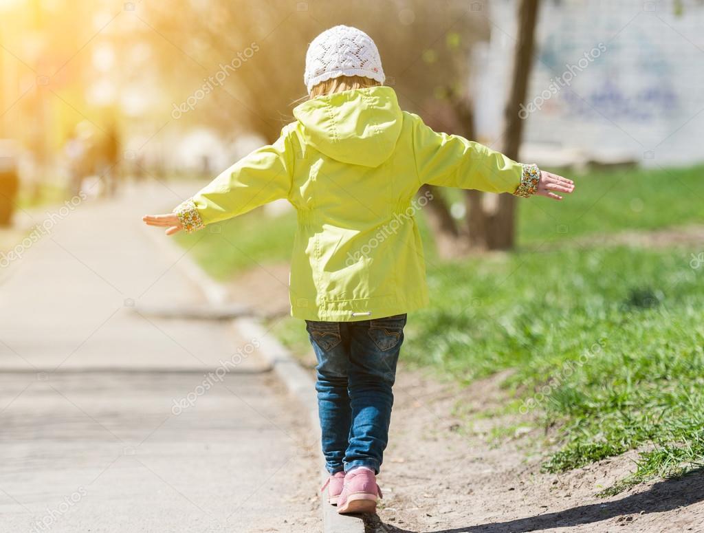 little girl in yellow coat walking in park