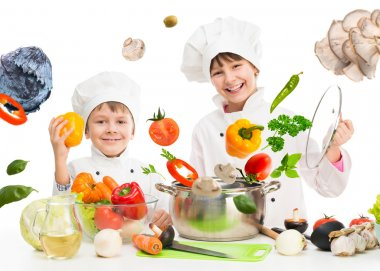 little chefs by table with flying vegetables
