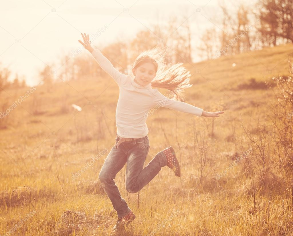 smiling little girl jumping on sunlight in countryside