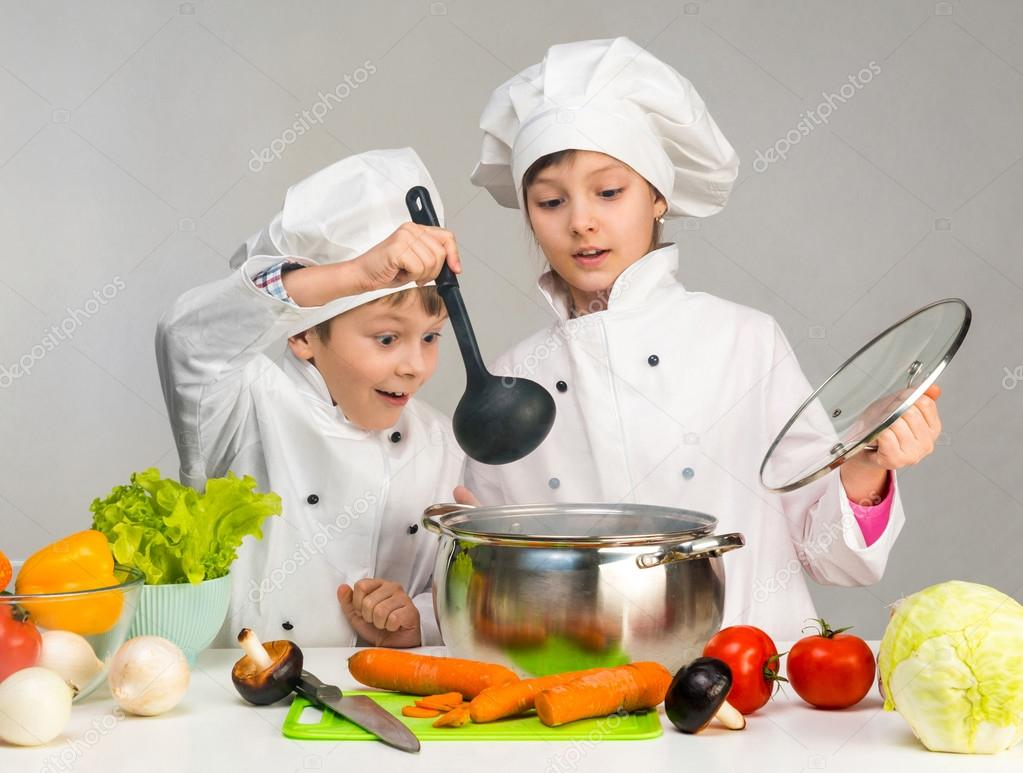 cooking little boy and girl looking in pan
