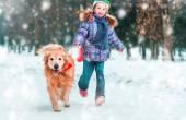 malá holčička se psem na sněhu v zimě