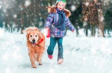 Little girl with dog on the snow in winter