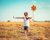Photo cute little girl with a  windmill