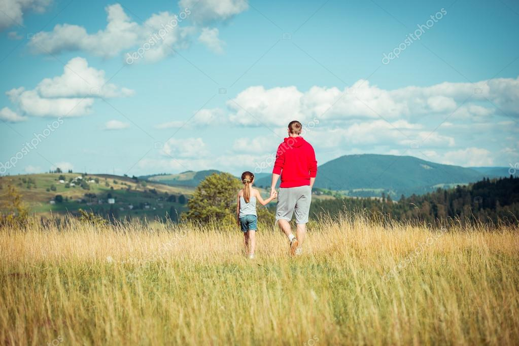 Family summer vacation in mountains. Active happy dad with his daughter having fun in travel