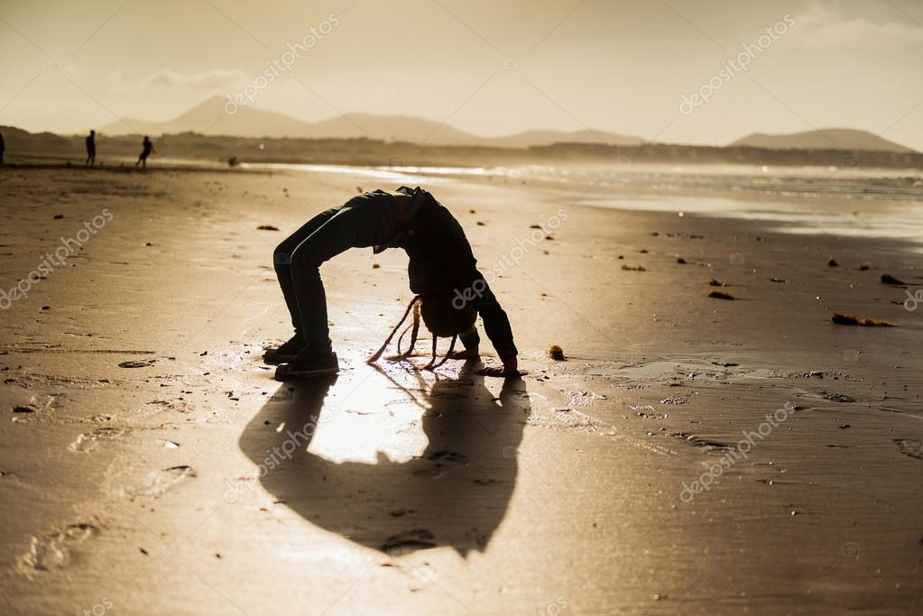 Little gymnast silhouette on beach