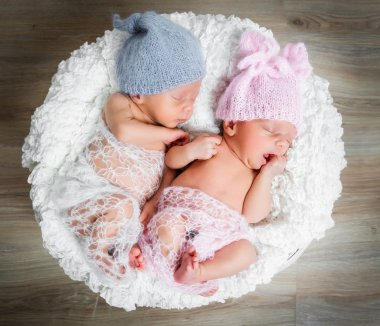 newborn twins l sleeping in a basket