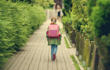 little girl with a backpack going to school