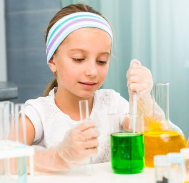 Cute little girl with flasks for chemistry stock vector