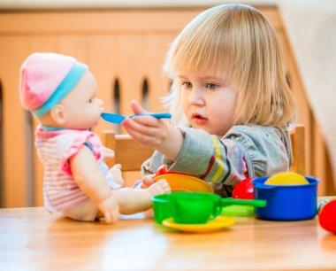 girl feeding a doll