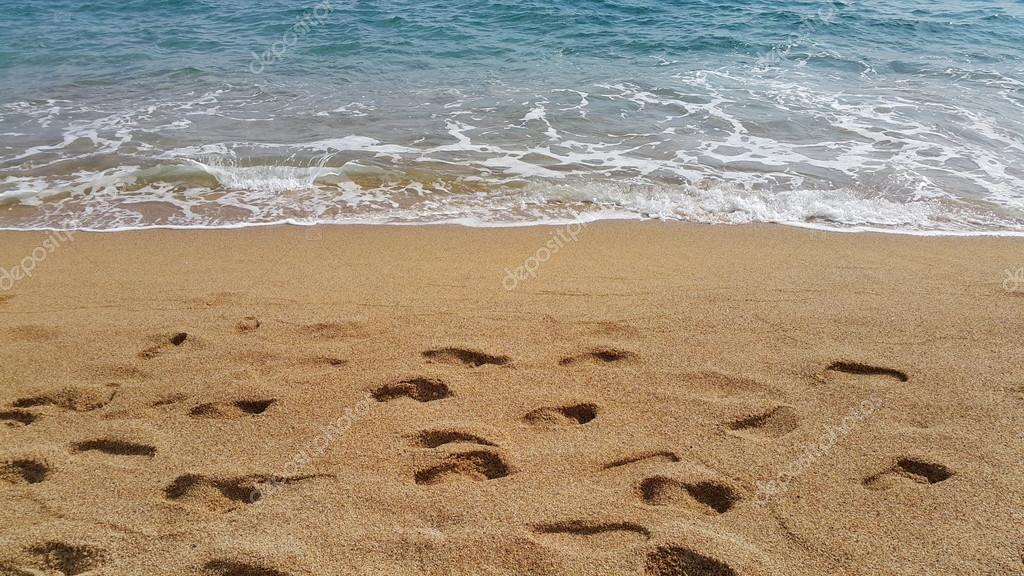 Waves and footprints on the sand beach