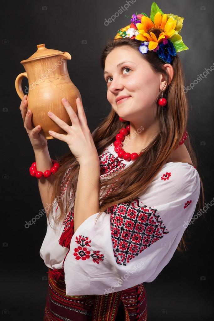 894979e6c528 Attraente donna indossa ucraino vestito nazionale è in possesso di una  brocca isolata su uno sfondo nero — Foto di bloodua
