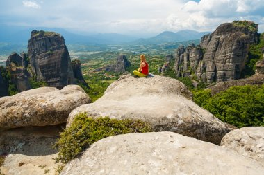 Girl meditating in Meteora, Greece