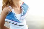 Fotografia Legato paio di sneakers che appende su una ragazza