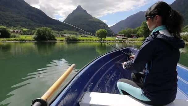 Woman on the boat catches a fish on spinning in Norway. Fishing in Norway is a way to embrace the local lifestyle. Countless lakes and rivers and an extensive coastline means outstanding opportunities
