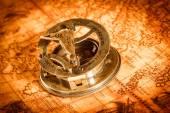 Fotografie Vintage compass lies on an ancient world map.