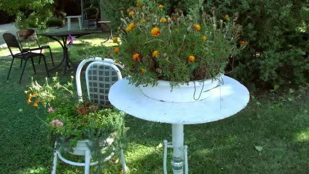 Tisch und Stühle mit Blumen im Garten
