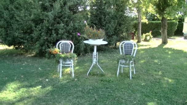 Stůl a židle s květinami v zahradě