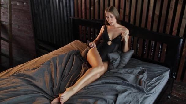 Frau Modell in schwarzen Dessous posiert auf dem Bett