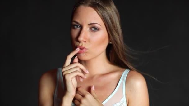 Model dívka v bílém prádle pózuje na černém pozadí