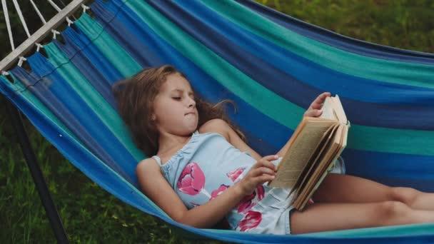Kudrnatá dívka čte knihu ležící v houpací síti