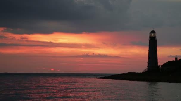 Maják na břehu moře a vypínat při západu slunce