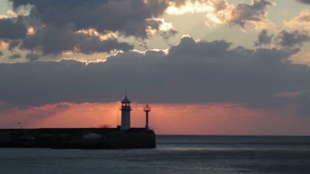 Sonnenaufgang in Jalta gegen einen Leuchtturm, Blick vom zentralen Damm