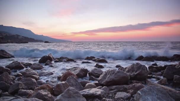 Hullámok megtörni a kövekről napkeltekor