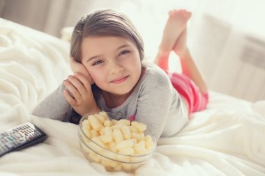 The cheerful girl eats popcorn and changes channels of the TV lying in a bed