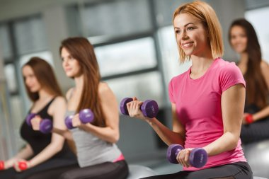 Sport girls in gym exercising with dumbbells